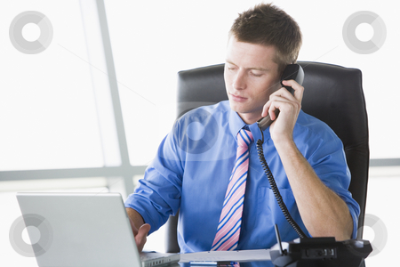 Businessman sitting in office with laptop on telephone stock photo,  by Monkey Business Images