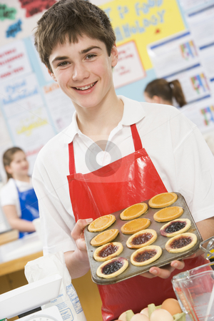 Schoolboy at school in a cooking class stock photo,  by Monkey Business Images