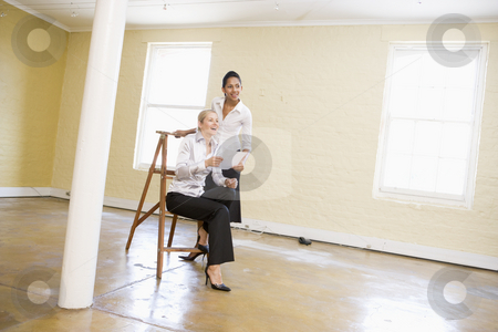 Two women in empty space with ladder holding paper and smiling stock photo,  by Monkey Business Images