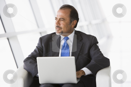 Businessman using laptop in lobby stock photo, Businessman using laptop in office lobby by Monkey Business Images