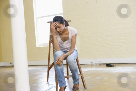 Woman sitting on ladder in empty space looking tired stock photo,  by Monkey Business Images