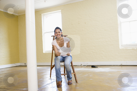 Woman sitting on ladder in empty space holding paper smiling stock photo,  by Monkey Business Images