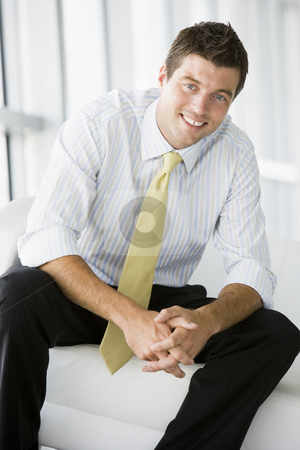 Businessman sitting in office lobby smiling stock photo,  by Monkey Business Images
