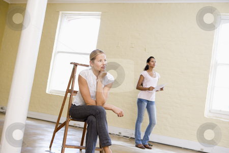 Two women with ladder in empty space holding paper stock photo,  by Monkey Business Images