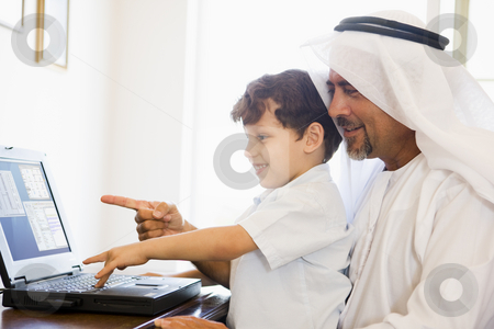 A Middle Eastern man and his son sitting in front of a computer  stock photo,  by Monkey Business Images