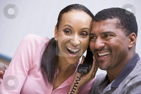 Couple receiving good news over phone stock photo, Couple receiving good news over phone at home by Monkey Business Images