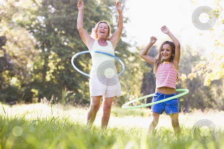 Grandmother and granddaughter at a park hula hooping and smiling stock photo,  by Monkey Business Images