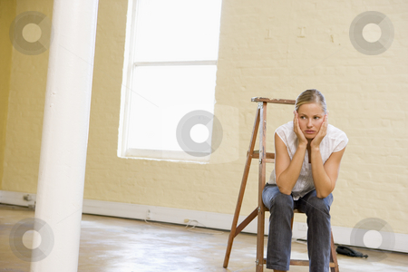 Woman sitting on ladder in empty space looking bored stock photo,  by Monkey Business Images
