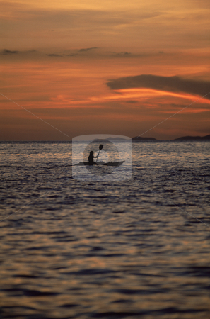 Silhouette of person kayaking at sea during sunset stock photo,  by Monkey Business Images