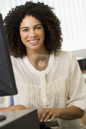 Mid adult woman working on a computer stock photo,  by Monkey Business Images