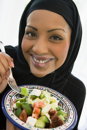 A Middle Eastern woman with a plate of salad stock photo,  by Monkey Business Images