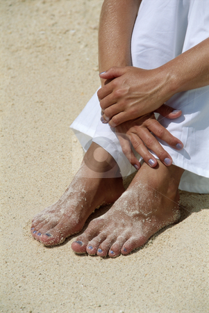 Young woman's feet covered in sand stock photo,  by Monkey Business Images