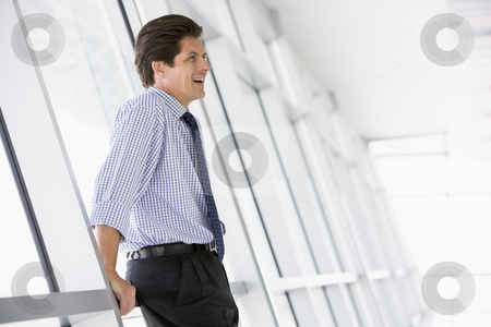 Businessman standing in corridor laughing stock photo,  by Monkey Business Images