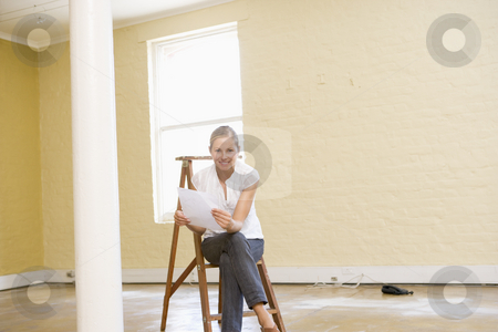 Woman sitting on ladder in empty space holding paper stock photo,  by Monkey Business Images