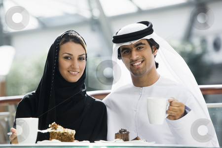 A Middle Eastern couple enjoying a meal in a restaurant stock photo,  by Monkey Business Images