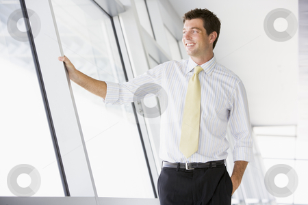 Businessman standing in corridor smiling stock photo,  by Monkey Business Images
