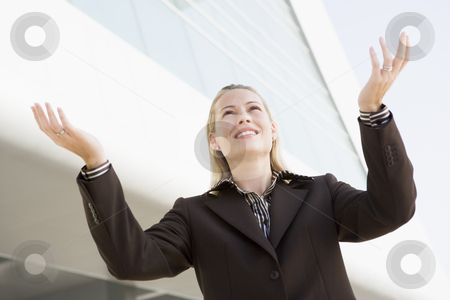 Businesswoman standing outdoors by building with hands out smili stock photo,  by Monkey Business Images
