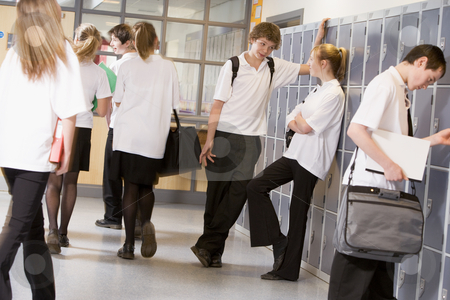 High school students by lockers in the school corridor stock photo,  by Monkey Business Images