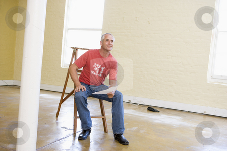 Man sitting on ladder in empty space holding paper stock photo,  by Monkey Business Images