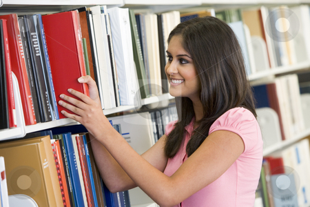 University student selecting book from library stock photo, Female university student selecting book from library shelf by Monkey Business Images