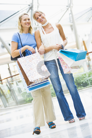 Friends shopping in mall stock photo, Friends shopping mall carrying bags by Monkey Business Images