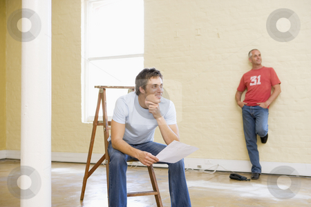 Two men with ladder in empty space one holding paper smiling stock photo,  by Monkey Business Images