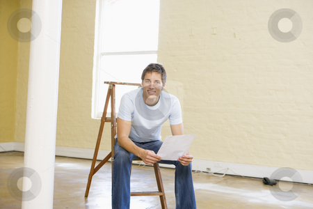 Man sitting on ladder in empty space holding paper smiling stock photo,  by Monkey Business Images