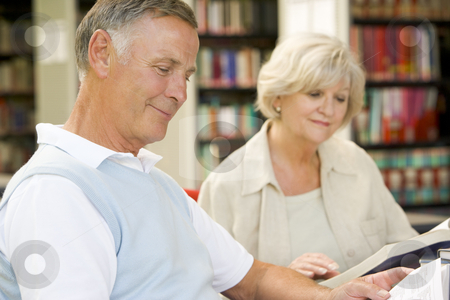 Adult students reading in a library stock photo,  by Monkey Business Images