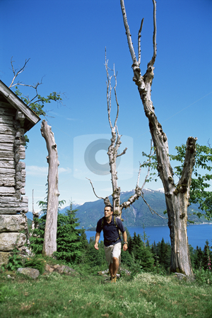 Man hiking up to a wooden cabin stock photo,  by Monkey Business Images