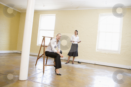 Two women with ladder in empty space holding paper smiling stock photo,  by Monkey Business Images