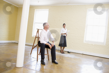 Man sitting on ladder in empty space with woman holding paper stock photo,  by Monkey Business Images