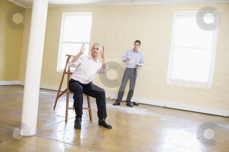 Two men with ladder in empty space making plans for room stock photo,  by Monkey Business Images