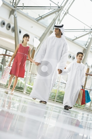 A Middle Eastern man with two children in a shopping mall stock photo,  by Monkey Business Images