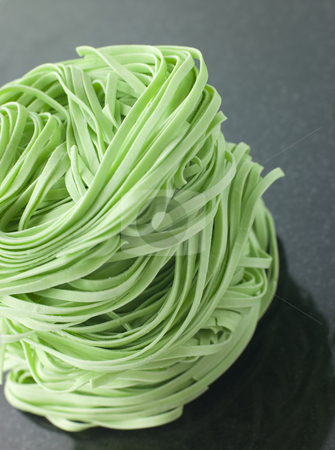 Stack of Spinach Noodles on a Black Background stock photo, Close up of Stack of Spinach Noodles on a Black Background by Monkey Business Images