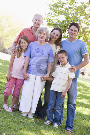 Extended family standing in park holding hands and smiling stock photo,  by Monkey Business Images