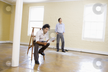 Man sitting on ladder in empty space holding paper with other ma stock photo,  by Monkey Business Images