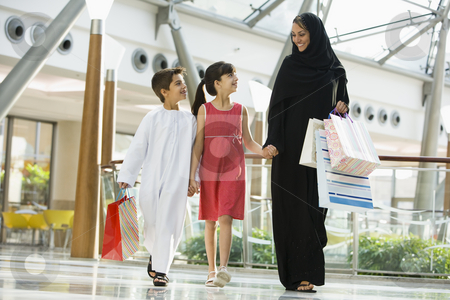 A Middle Eastern woman with two children in a shopping mall stock photo,  by Monkey Business Images