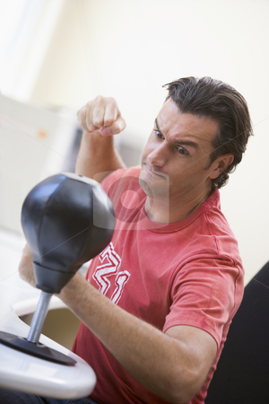 Businessman in office using small punching bag to relieve stress stock photo,  by Monkey Business Images