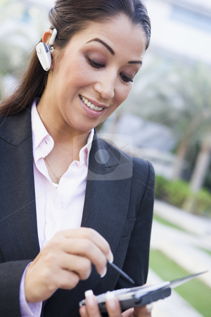 Businesswoman using bluetooth earpiece and PDA stock photo, Businesswoman using bluetooth earpiece and PDA outside by Monkey Business Images