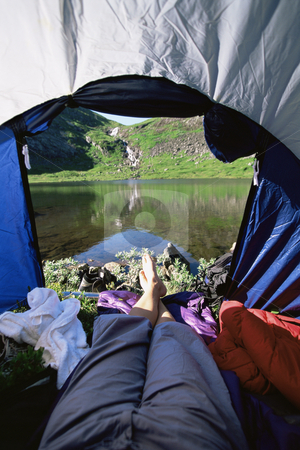 Woman lying in tent with a view of lake stock photo,  by Monkey Business Images
