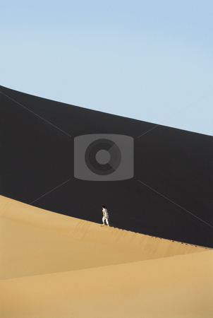 Woman walking across desert sand dunes stock photo,  by Monkey Business Images