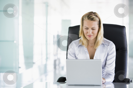Businesswoman in office using laptop stock photo,  by Monkey Business Images