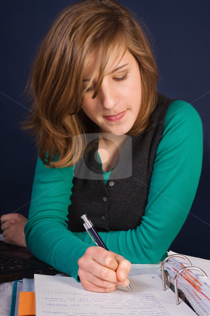 Student at work stock photo, Teenager girl writing her homework in a notepad by Mikhail Lavrenov
