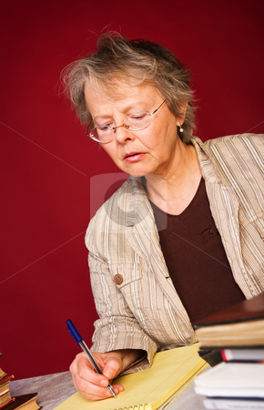 Researcher with her books and notes stock photo, Mature woman taking notes in her note pad by Mikhail Lavrenov