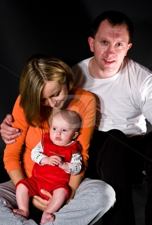 Parents with baby girl stock photo, Portrait of a happy couple holding a baby by Mariusz Jurgielewicz