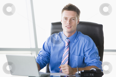 Businessman sitting in office with laptop stock photo,  by Monkey Business Images