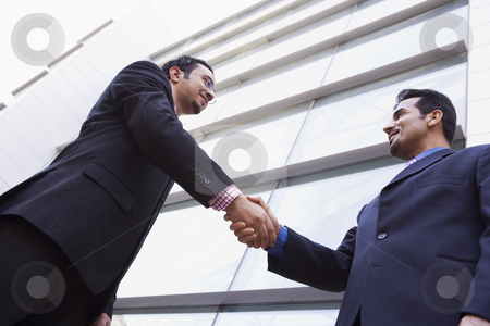Two businessmen shaking hands outside office building stock photo, Two businessmen shaking hands outside modern office building by Monkey Business Images