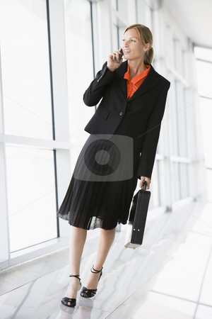 Business woman walking in corridor talking on cellular phone stock photo,  by Monkey Business Images
