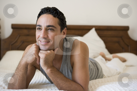 A Middle Eastern man lying on a bed stock photo,  by Monkey Business Images