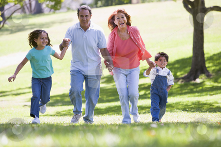 Grandparents running with grandchildren stock photo,  by Monkey Business Images